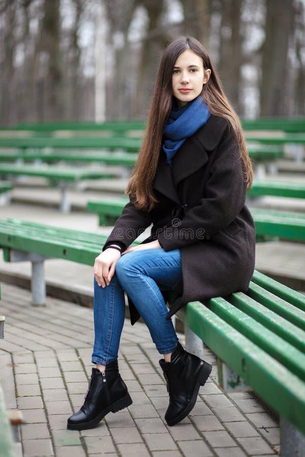 一条黑外套蓝色围巾玻璃的年轻美丽的女孩坐长凳在城市公园 有华美的extr的一个典雅的深色的女孩 库存照片