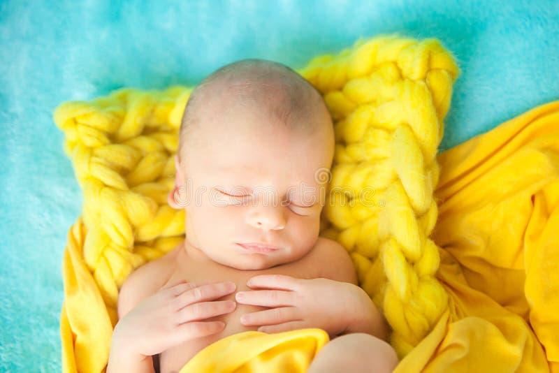 一条黄色大块的编织毯子的睡觉的逗人喜爱的新出生的婴孩 免版税库存图片