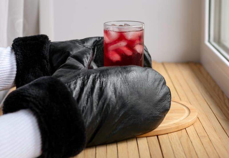 一杯与从冬天窗口采取的冻冰块的冷淡的冰樱桃汁在冷却以后 在厨师的手上 免版税库存图片