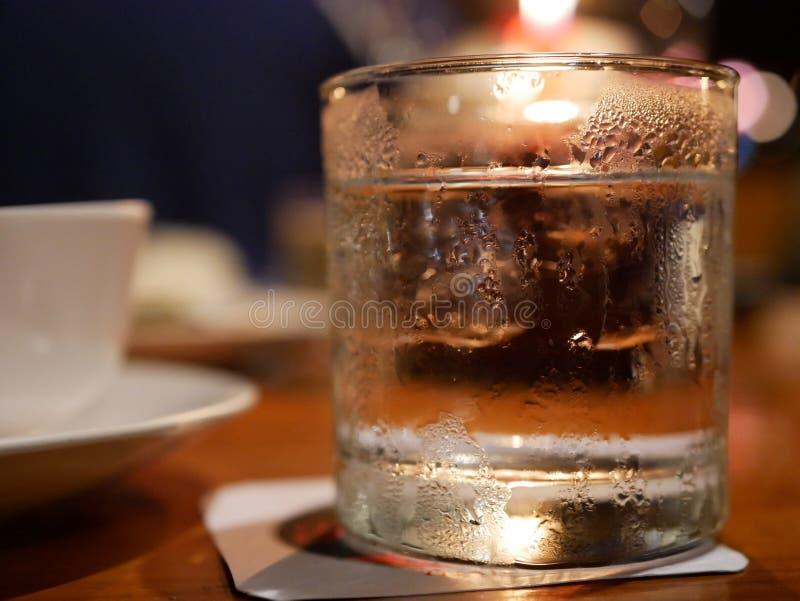 一杯与冰的水在与蜡烛光的一张dinning的桌上 免版税库存图片