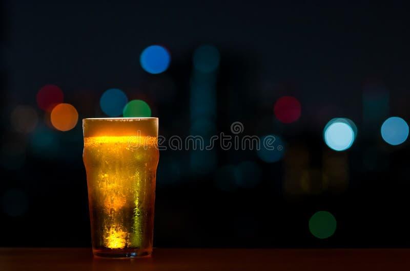 一杯与它的泡沫的啤酒在与五颜六色的bokeh光的黑暗的夜背景隔绝的酒吧的木桌投入  免版税库存照片