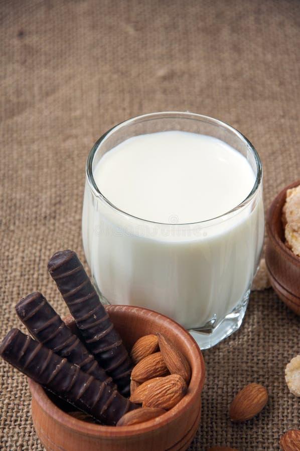 一杯与杏仁坚果,玉米片,巧克力的牛奶,在粗麻布,袋装背景 库存图片