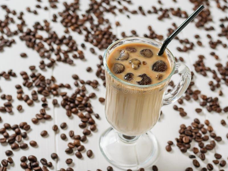 一杯冰冻咖啡和一支鸡尾酒管在疏散咖啡豆背景在一张白色桌上 库存图片