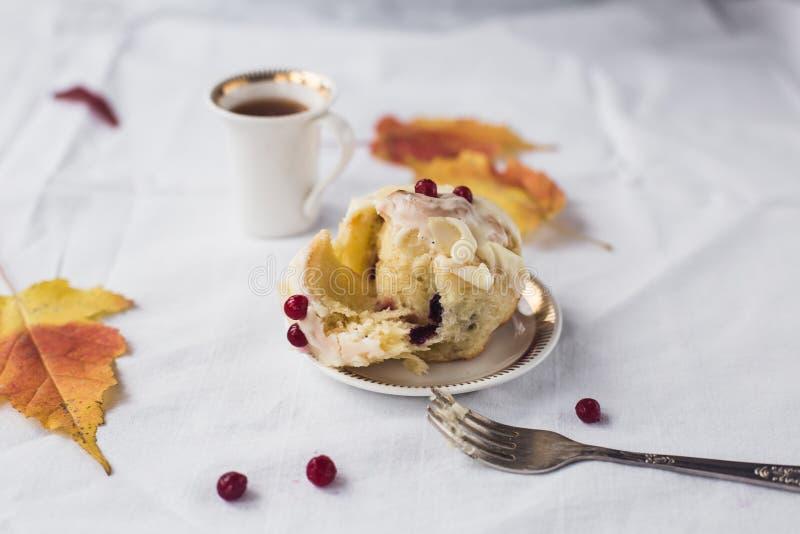 一杯咖啡、桂香小圆面包和黄色叶子 免版税库存照片