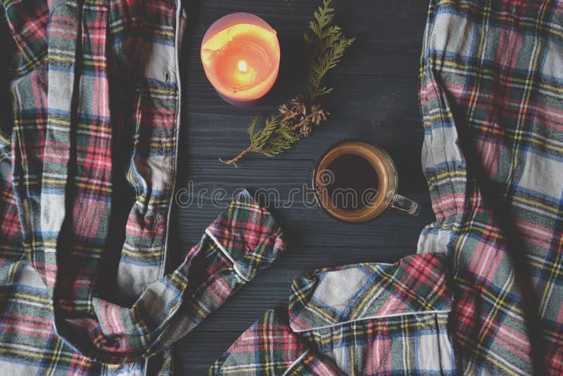 一杯咖啡、睡衣和被点燃的蜡烛在木背景 舒适家庭样式 大气图片 库存图片