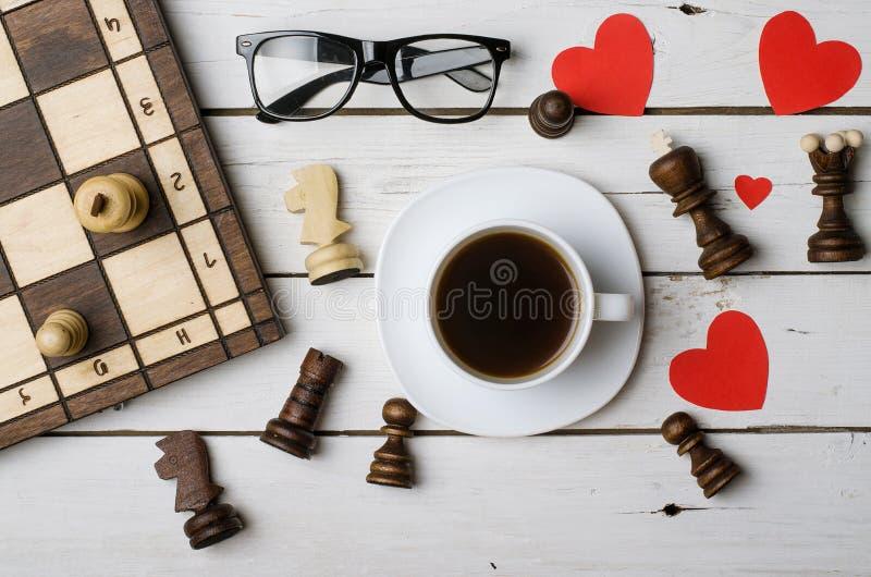 一杯咖啡、玻璃和棋子在一张木桌上,上面 免版税图库摄影