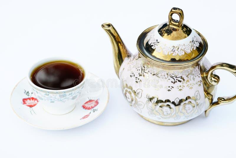 一杯咖啡和在一个咖啡水壶旁边有白色背景 免版税库存照片
