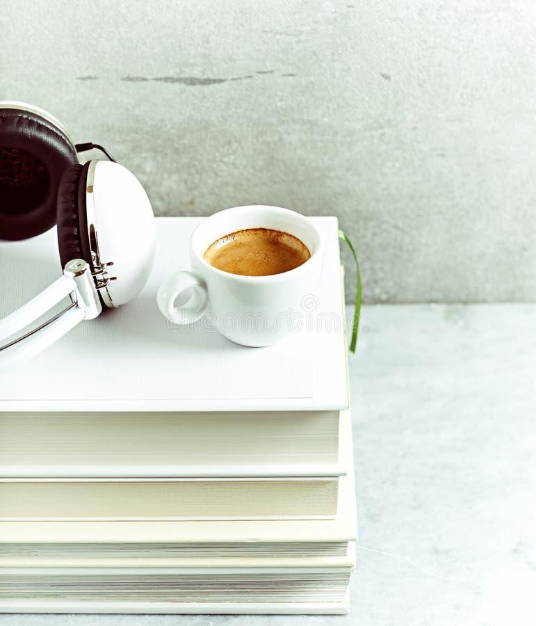 一杯咖啡和耳机在堆书 免版税库存图片