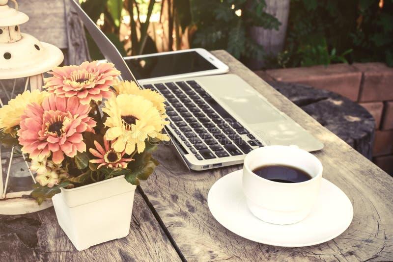 一杯咖啡和膝上型计算机在木地板上与花 库存照片