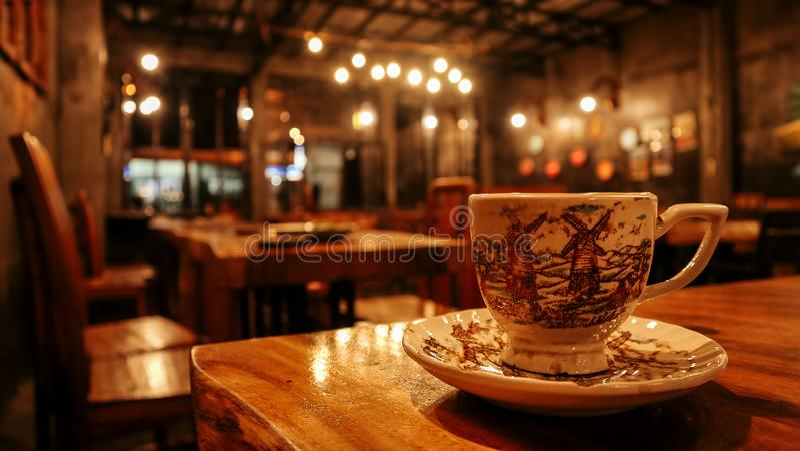 一杯咖啡在与一镇静气氛咖啡馆的一张木桌上服务 免版税图库摄影