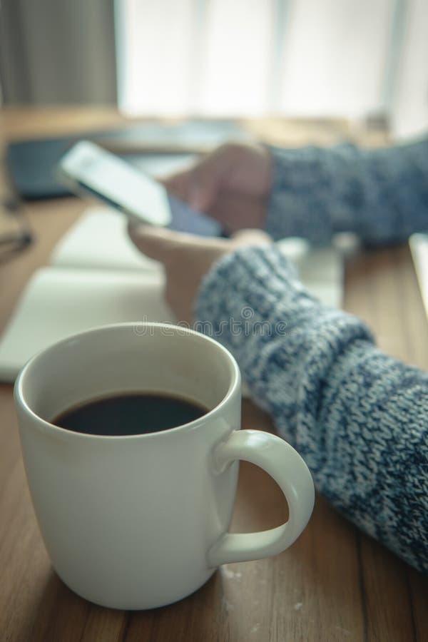 一杯咖啡在木桌上的 简单的工作区在家 免版税库存照片