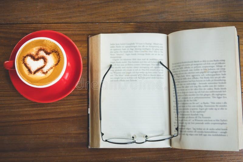 一杯咖啡热奶咖啡或拿铁与开放书和玻璃o 库存图片