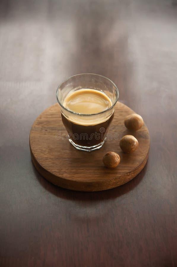 一杯咖啡用在圆的木盘子的马卡达姆坚果在木书桌上 简单的工作区,咖啡休息早晨 库存照片