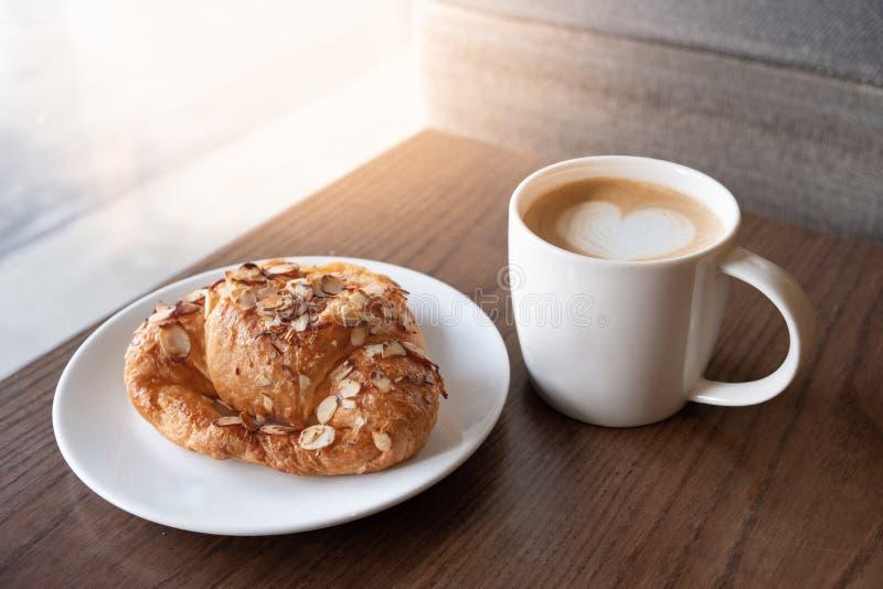 一杯咖啡用在早晨光的杏仁新月形面包 免版税库存照片
