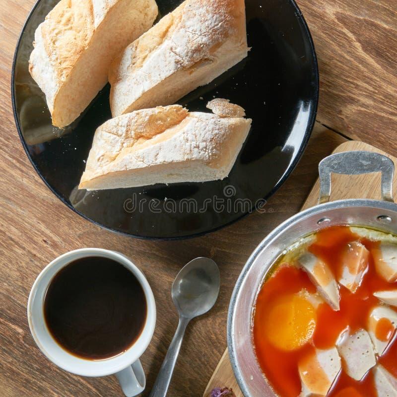 一杯咖啡用新鲜的切的意大利面包和被批评的鸡蛋a 免版税库存图片