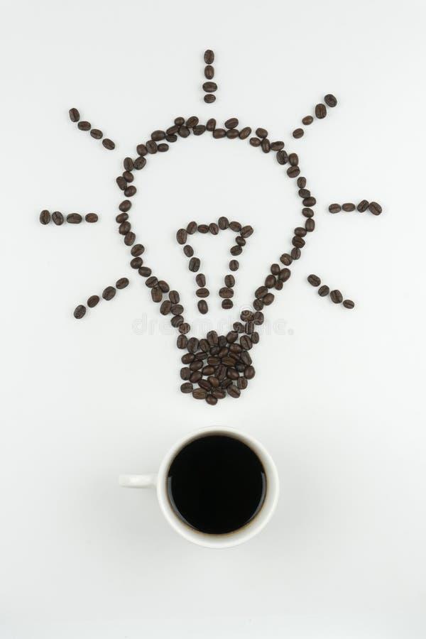一杯咖啡的顶视图与在电灯泡标志安排的烤咖啡豆的 免版税库存照片