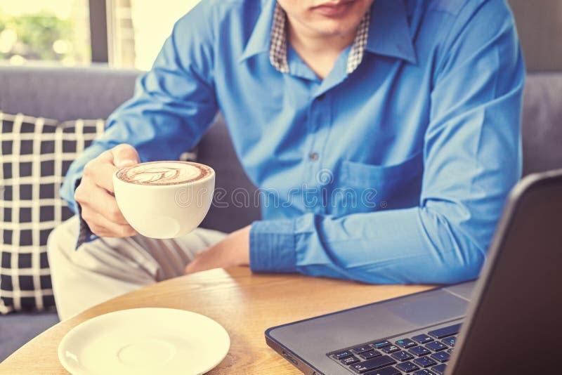 一杯商人举行咖啡 一杯咖啡在桌上在膝上型计算机附近 图库摄影