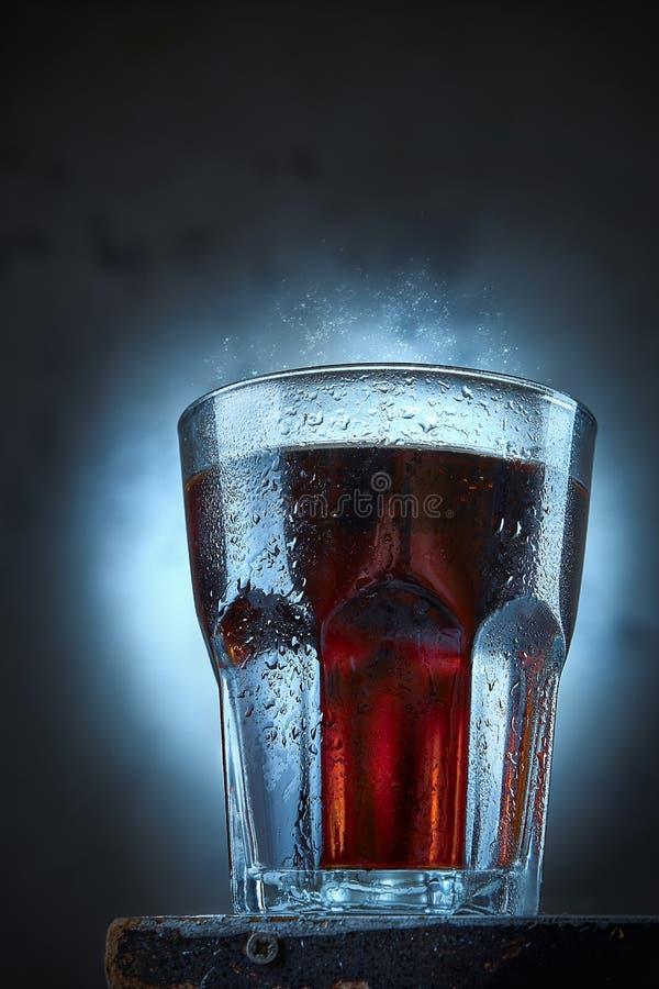 一杯在一个混凝土墙前面的可乐立场 焦炭冷玻璃杯与下落的在它和嘶嘶响 夏天饮料概念 ?? 库存图片