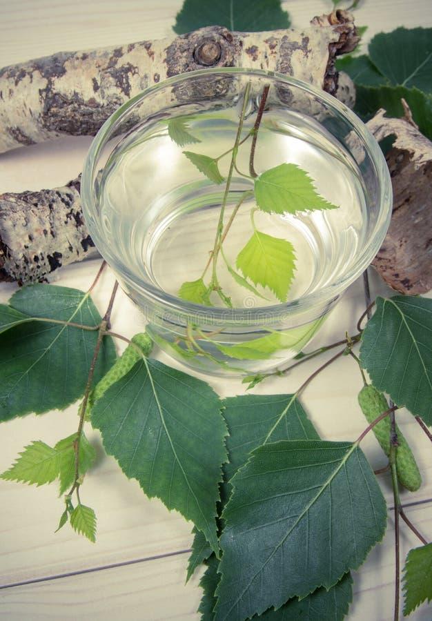 一杯在木背景的桦树汁液 免版税库存图片