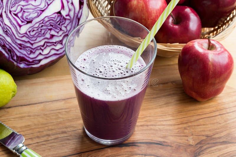 一杯在桌上的紫色圆白菜汁 免版税图库摄影