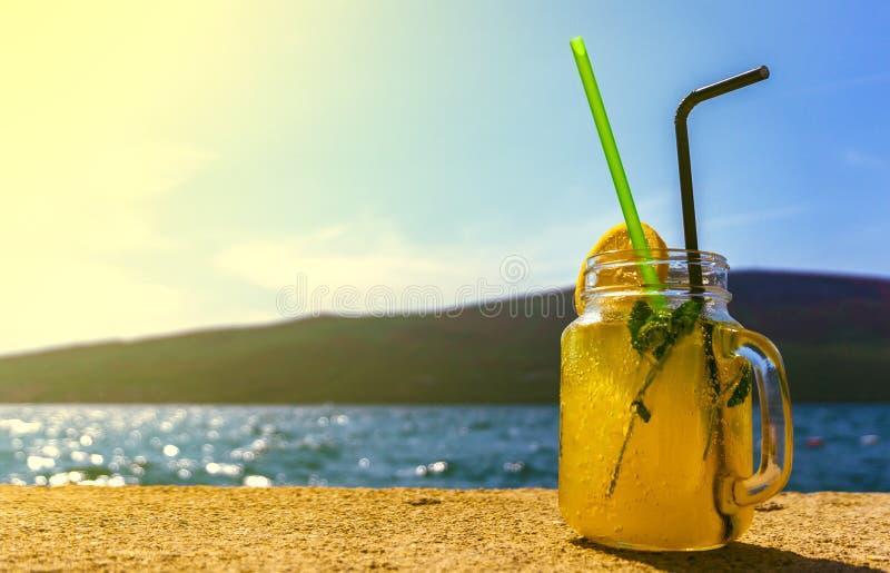 一杯在海的背景的鸡尾酒好天气的 免版税库存图片