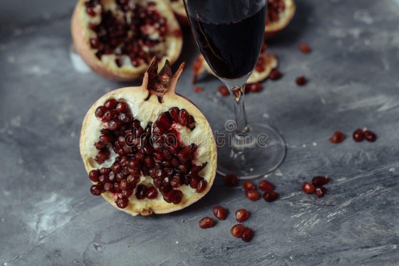 一杯在灰色背景的酒在石榴中 接近的石榴和红色石榴种子 免版税库存照片