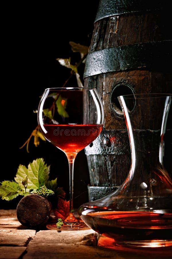 一杯在蒸馏瓶旁边的红葡萄酒 库存图片