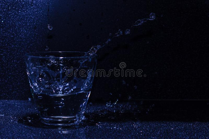 一杯在黑暗的背景的水飞溅 图库摄影
