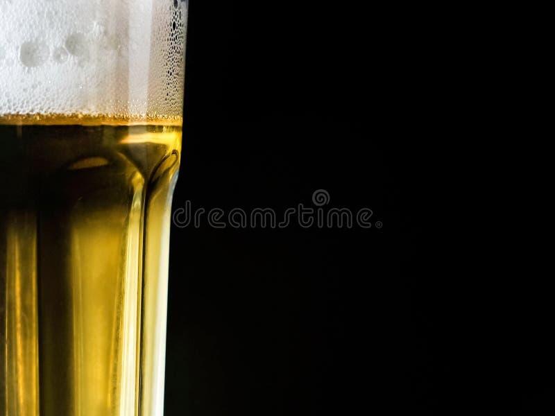 一杯在黑背景的啤酒 免版税库存图片