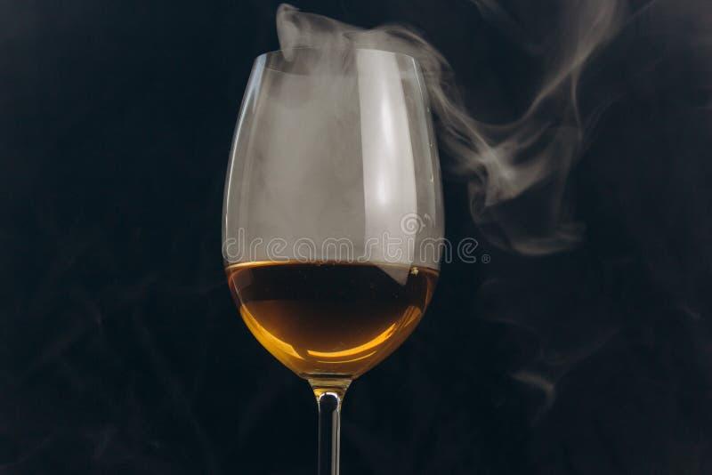 一杯在黑背景的白酒 从水烟筒的烟包围玻璃 休息,假日 酒精饮料特写镜头 免版税库存照片