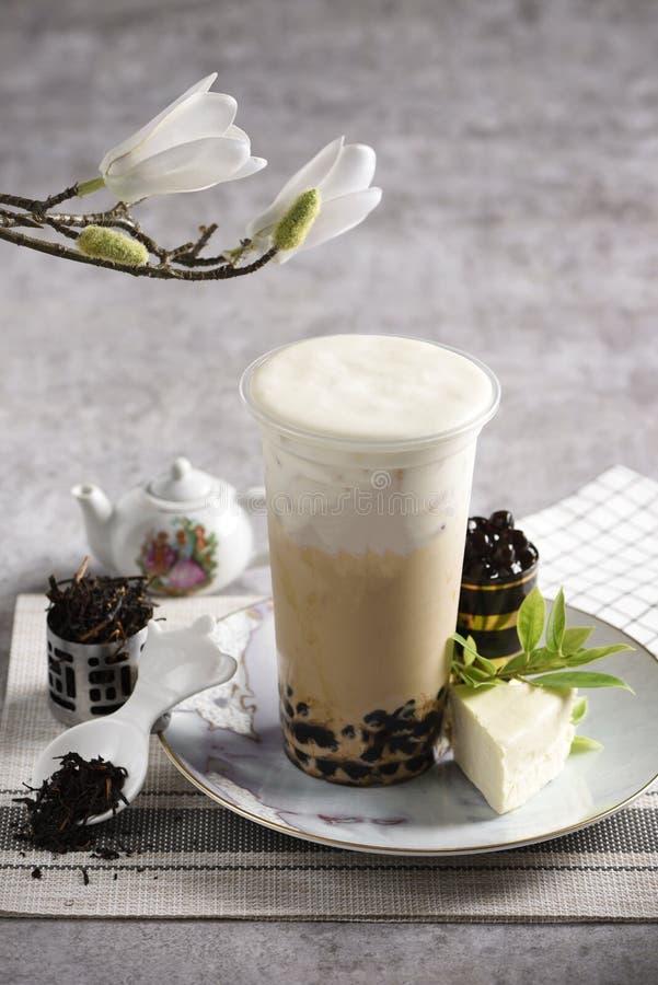 一杯奶茶 那里在板材和一个小的绿茶罐的一些被切的石灰 库存照片