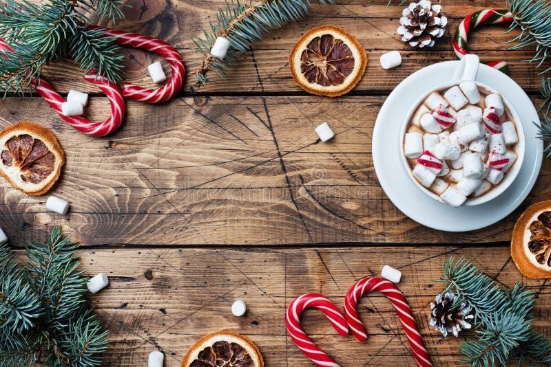 一杯带棉花糖的热巧克力 圣诞树和装饰、甘蔗焦糖和橙子坚果木质背景 库存图片