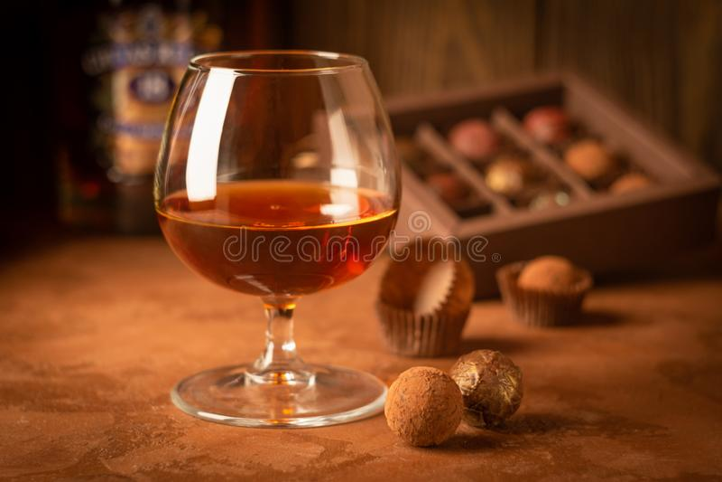 一杯强的酒精饮料白兰地酒或白兰地酒和一箱在黑暗的背景的巧克力 选择聚焦 免版税库存图片