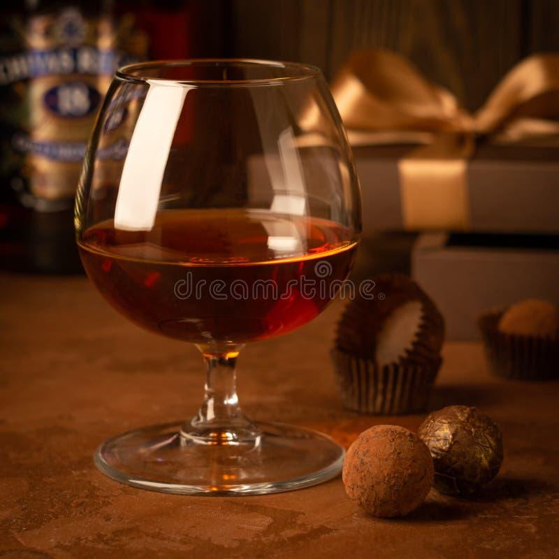 一杯强的酒精饮料白兰地酒或白兰地酒和一箱在黑暗的背景的巧克力 选择聚焦 库存图片