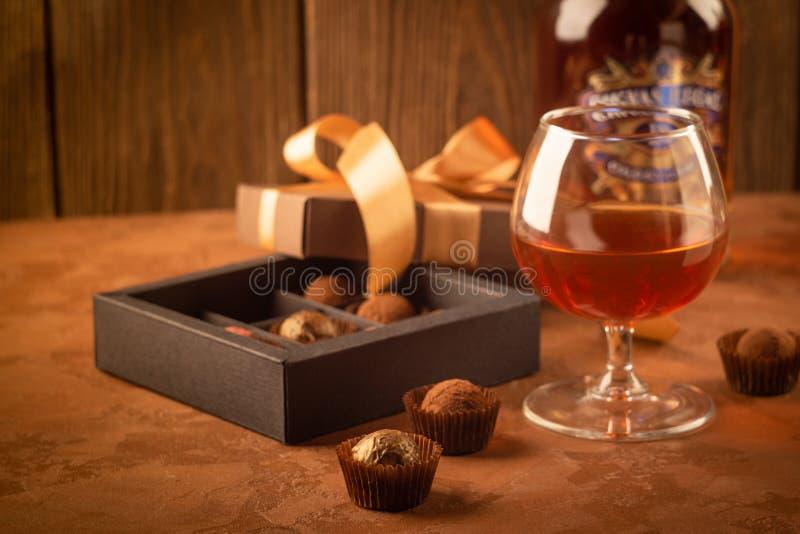 一杯强的酒精饮料白兰地酒或白兰地酒和一箱在黑暗的背景的巧克力 免版税库存照片