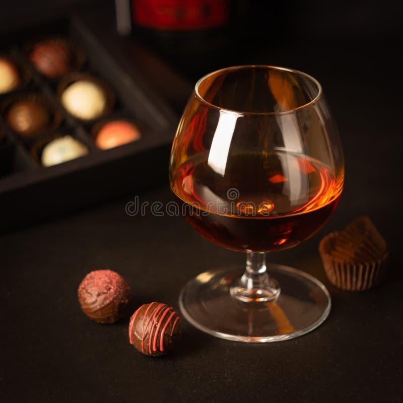 一杯强的酒精饮料白兰地酒或白兰地酒和糖果由比利时巧克力制成在黑暗的背景 免版税图库摄影
