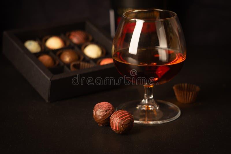 一杯强的酒精饮料白兰地酒或白兰地酒和糖果由比利时巧克力制成在黑暗的背景 库存图片