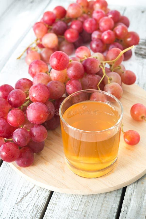 一杯新鲜的葡萄汁和一束红葡萄 图库摄影