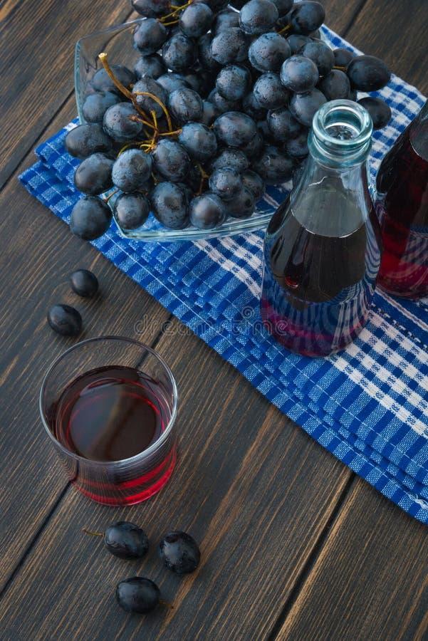 一杯新鲜的葡萄汁和一束黑葡萄 库存照片