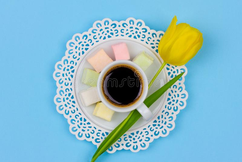 一杯无奶咖啡、蛋白软糖在茶碟和一朵黄色郁金香花在一张蓝色背景特写镜头顶视图 免版税库存照片