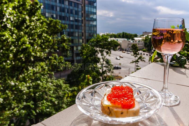 一杯桃红葡萄酒和面包用红色鱼子酱在栏杆 免版税图库摄影