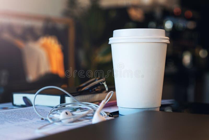 一杯白皮书咖啡的特写镜头在一张桌上的在没有人的一个空的咖啡馆 附近耳机和笔记本 o 免版税库存照片