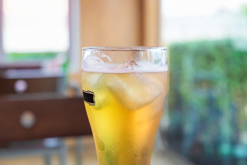 一杯的一半低度黄啤酒在餐馆 库存照片