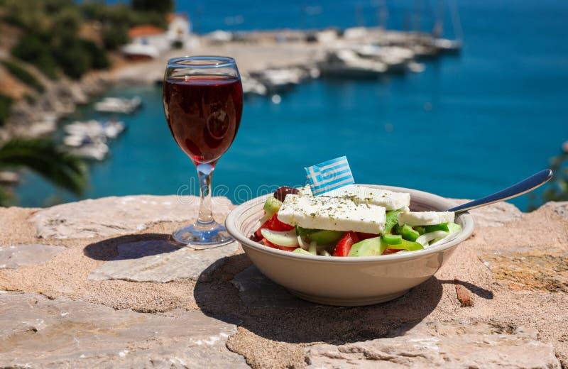 一杯红葡萄酒和碗与希腊旗子的希腊沙拉由海视图,夏天希腊假日概念 免版税库存照片