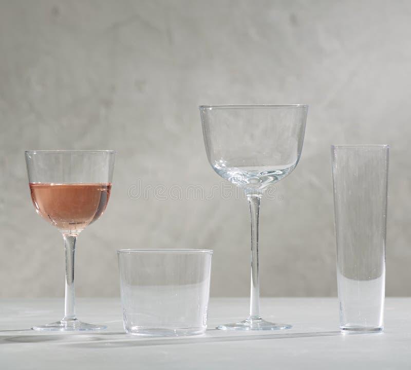 一杯红酒和四个空的酒杯、一杯红酒和四个空的酒杯 库存照片