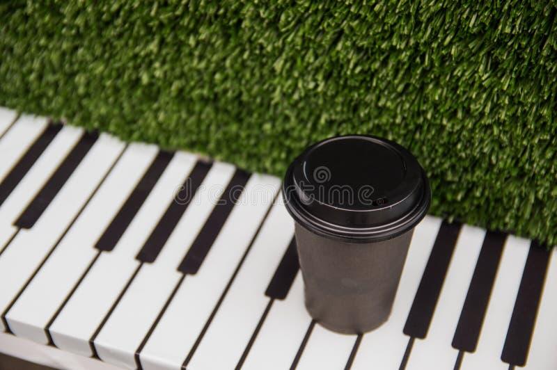 一杯纸咖啡在一架钢琴的钥匙的立场在绿色象草的背景的 库存照片