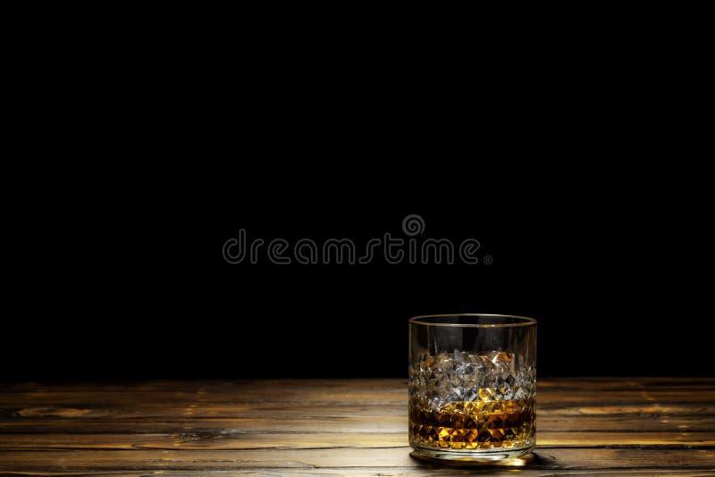 一杯苏格兰威士忌酒或威士忌酒在岩石与冰在木桌上在黑背景中 免版税库存照片