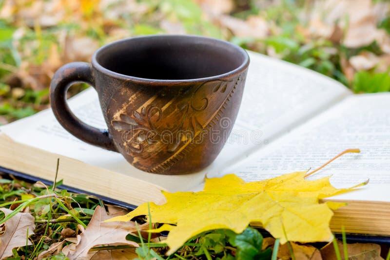 一杯茶或咖啡和一黄色枫叶在一本开放书在秋天在森林 休息和读在nature_的一本书 免版税图库摄影