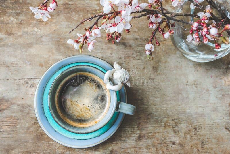 一杯葡萄酒蓝色咖啡的顶视图与一个天使小雕象和一个花瓶的有在木背景的开花的树枝的 免版税库存图片