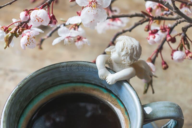 一杯蓝色葡萄酒咖啡的顶视图与天使小雕象和春天树枝的在木背景 免版税库存图片